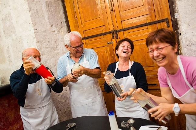 Bei einem Kochkurs mixen Gäste einen Cocktail und lachen sich kaputt. Versuche es auch einmal und lebe wie die Einheimischen auf deiner Südamerika Reise