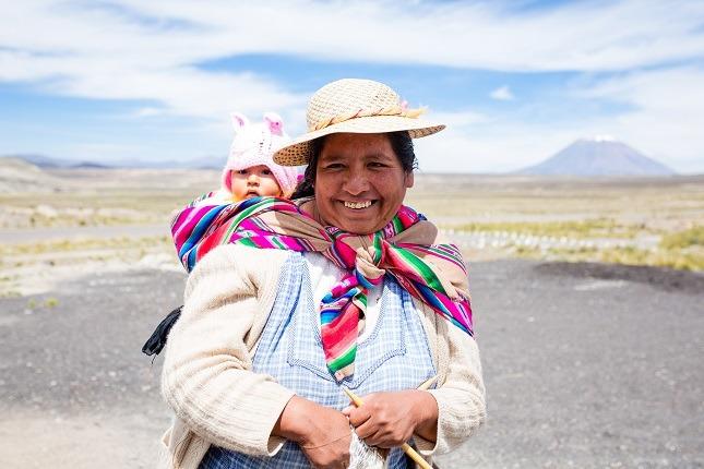 Eine Mutter hat ihr Baby mit einem bunten Tuch auf den Rücken gebunden und lacht in die Kamera.
