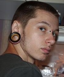 Ein junger Mann mit Ear Plugs - gedehnten Ohrläppchen
