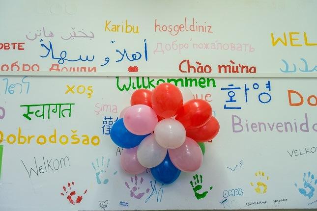 """Die weiße Wand im Haus D ist bunt bemalt. In allen Sprachen steht dort """"Willkommen""""."""