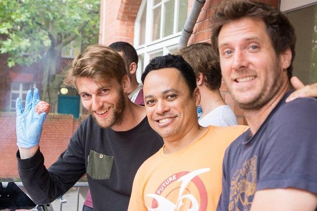 Beim Viventura Sozialtag in Berlin stehen Viventura Mitarbeiter vor dem Grill und lächeln in die Kamera.