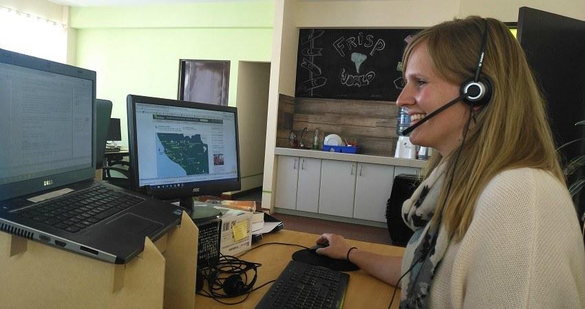 Praktikum in La Paz. Sarah sitzt an ihrem Schreibtisch und spricht mit einem Kunden über ihr Headphone.