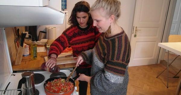 Empanadas Rezept aus Chile: Felia steht am Herd und rührt die Tomaten-Oliven Füllung der Empanadas. Alice gibt Kidneybohnen dazu.,