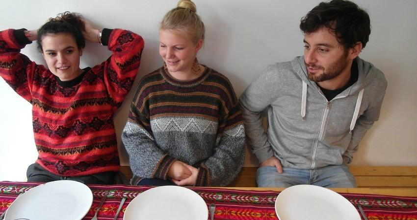 Empanadas Rezept aus Chile: Alice, Felia, Nino (v.l.) sitzen am gedeckten Tisch.