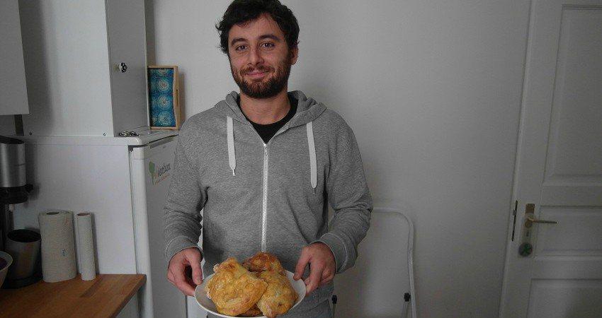 Empanadas Rezept aus Chile: Nino steht mit einem Teller frisch gebackener Empanadas in der Viventura Küche und posiert für die Kamera.