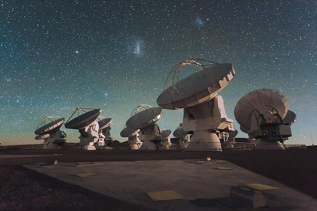 The_Atacama_Large_Millimeter_Array_(ALMA)_by_night,_under_the_Magellanic_Clouds