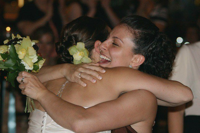 Zwei Freundinnen umarmen sich zur Begrüßung auf einer Hochzeit.