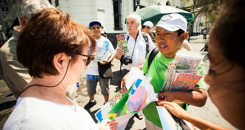 Lerne Spanisch auf deiner Südamerikareise. Die Reisegruppe fragt eine Peruanerin nach dem Weg.