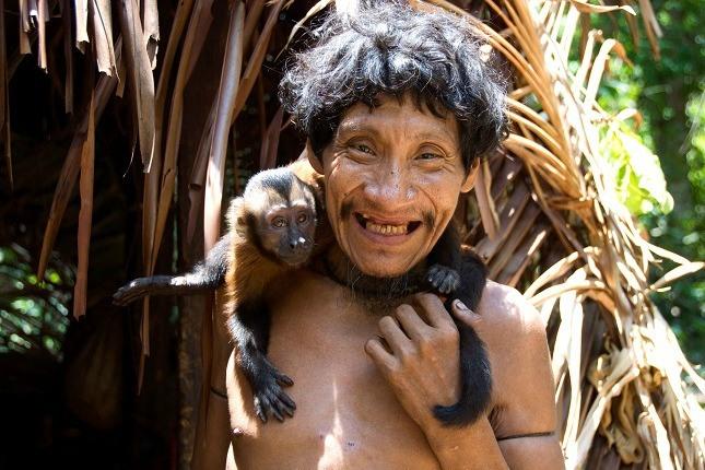 Indigene Völker im Amazonasgebiet: Ein Mitglied des Awá-Stammes hat einen Affen auf den Schultern und lacht in die Kamera.