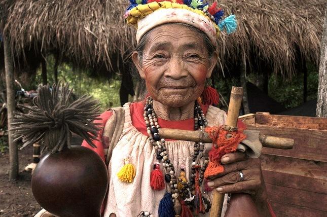 Indigene Völker im Amazonasgebiet: Die Guarani Großmutter trägt viel Schmuck und präsentiert ihre Musikinstrumente.