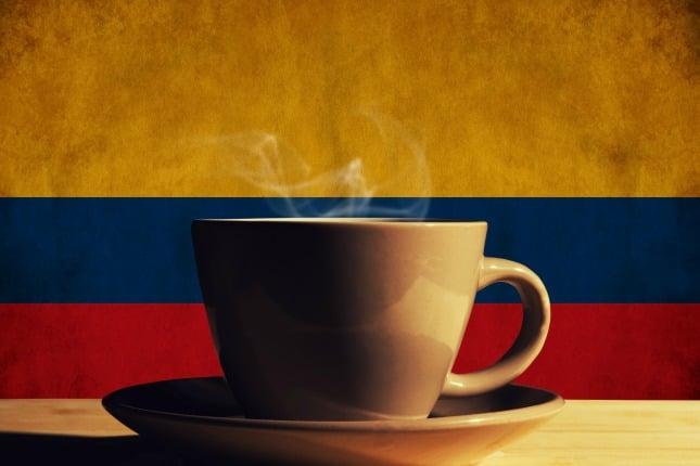 Tasse Kaffee mit kolumbianischer Flagge im Hintergrund