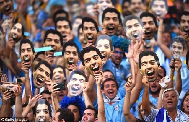 Gare aux morsures ! Les fans de l'Uruguay brandissent des masques de Luis Suarez avant de jouer contre la Colombie ©Getty