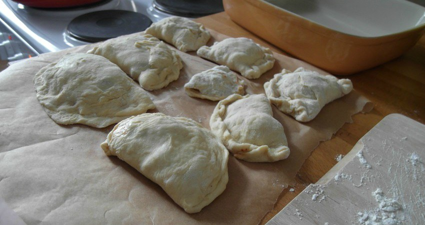 Empanadas Rezept aus Chile: Ein Blech mit rohen Empanadas ist bereit in den Ofen geschoben zu werden.